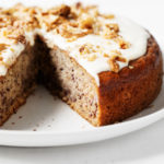 A round vegan banana cake with cashew frosting has been sliced into on a serving plate.