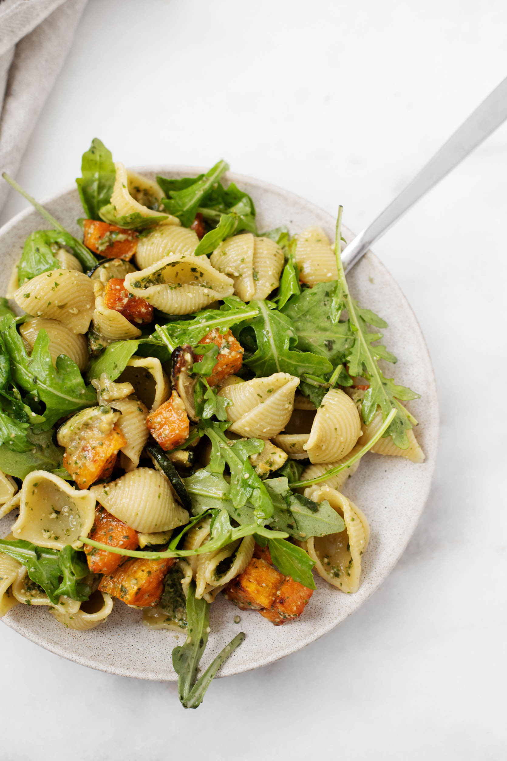 A zoomed in photograph of a plate of pasta shells made with roasted vegetables, arugula, and pesto sauce.