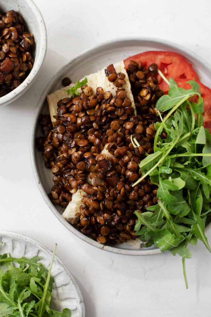 An overhead shot of sliced toast with red wine braised lentils and fresh arugula.