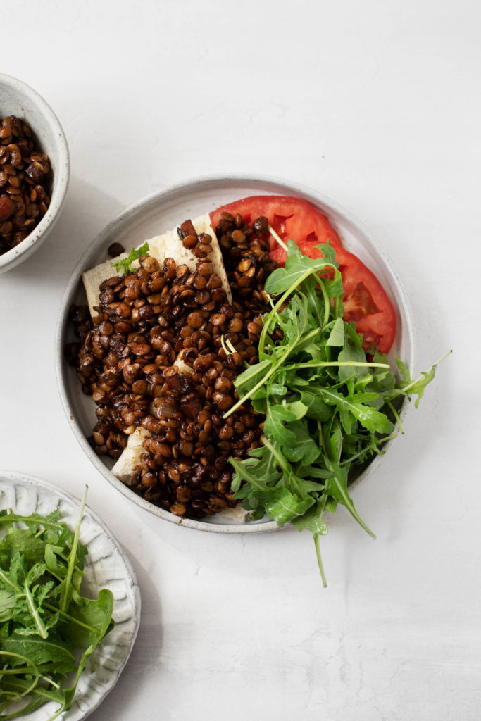 An overhead shot of red wine braised lentils on toast, served with greens and tomato.