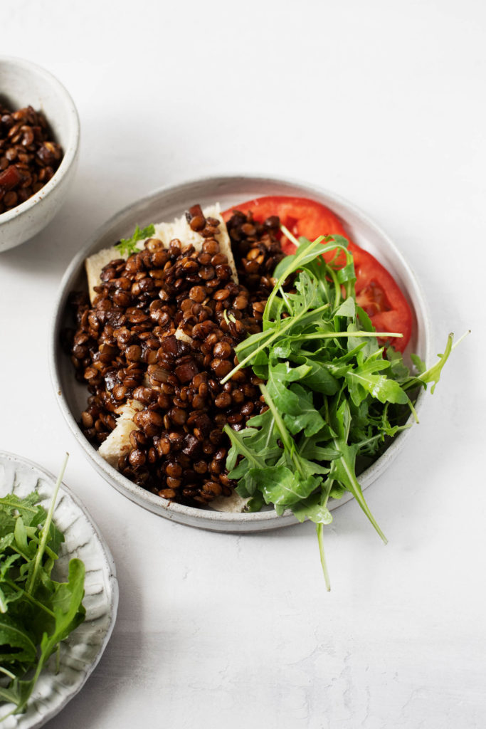 Braised lentils on toast, served with fresh, late summer tomato and arugula.