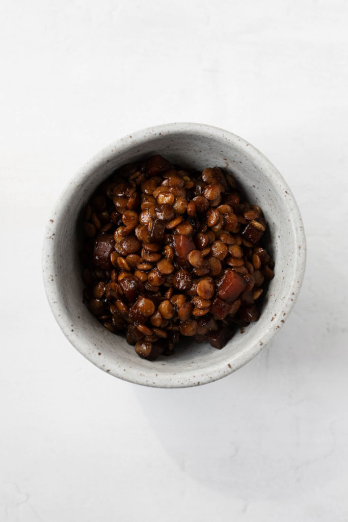 A small bowl of lentils that have been braised in red wine.