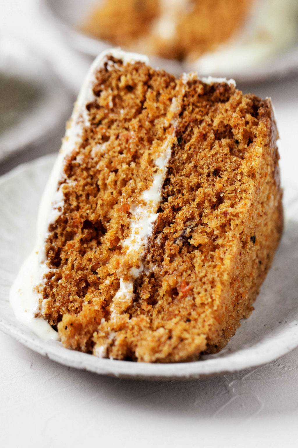 A big slice of carrot pumpkin cake, studded with raisins and walnuts.