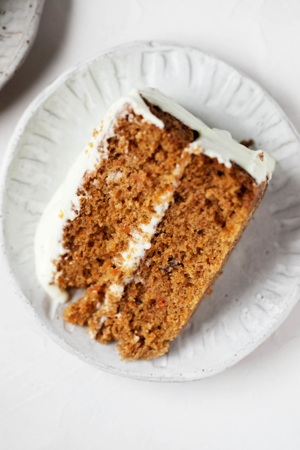 An overhead photograph of a dessert plate with a slice of vegan pumpkin carrot cake, lightly frosted with cream cheese frosting.