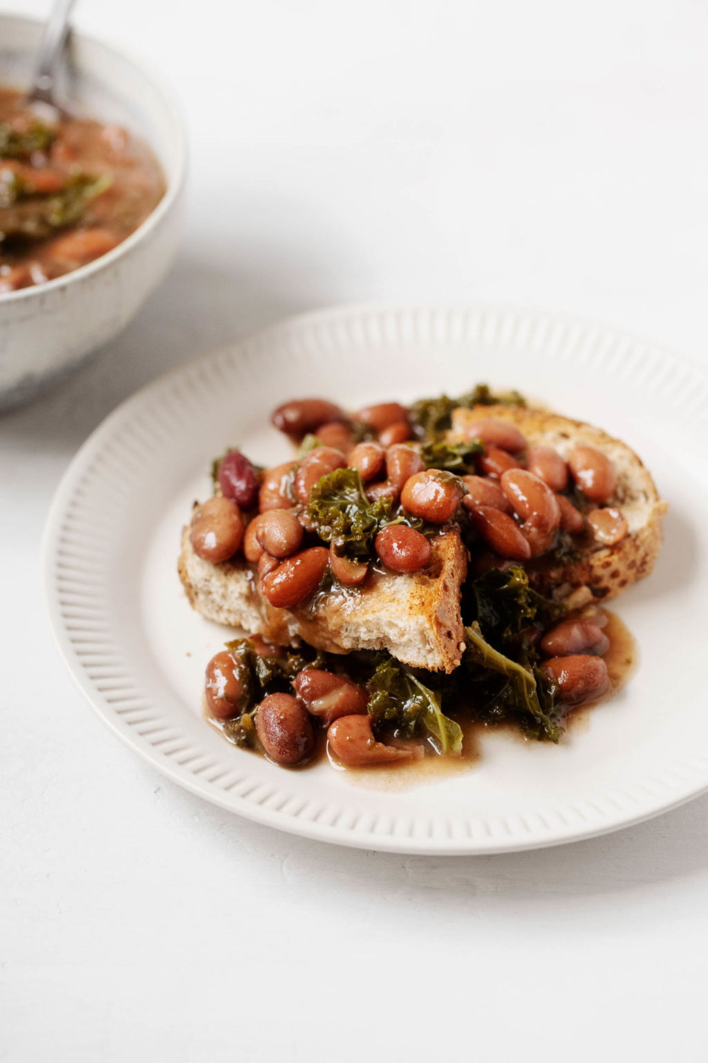 A white serving plate holds toast that has been smothered with braised beans and kale. A bowl with additional ingredients peeks out in the background.