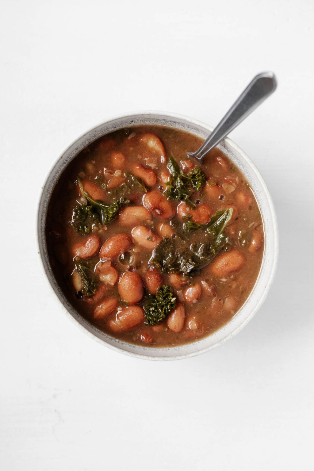 A white bowl is filled with soupy cooked cranberry beans and kale.