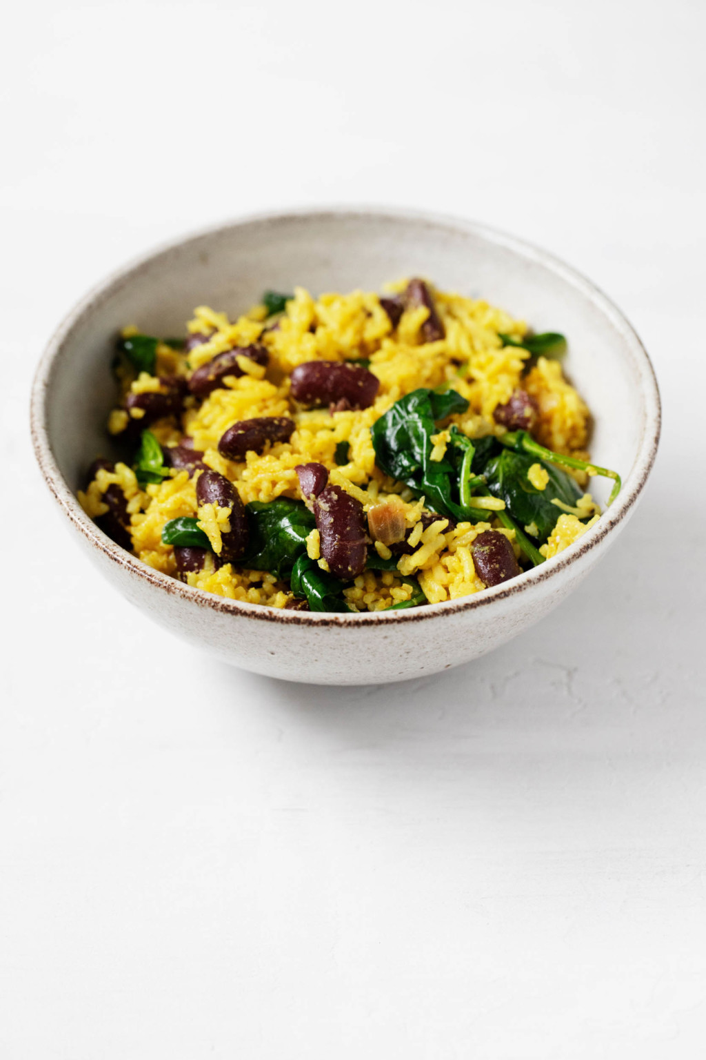 A small, ceramic bowl holds a plant-based meal of kidney beans, whole grains, and spinach.