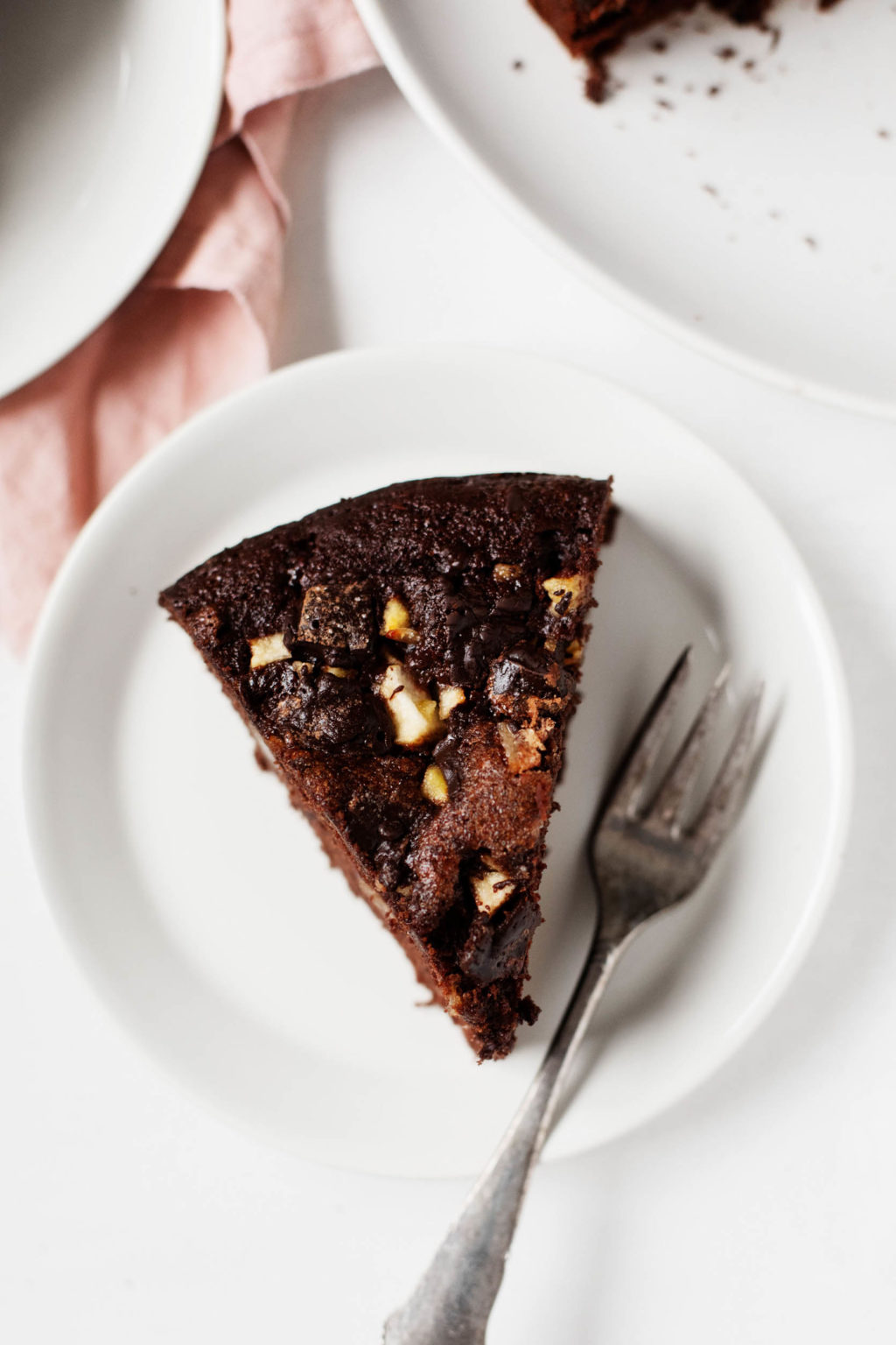 A neat slice of festive chocolate pear cake is perched on a dessert plate, with a small fork for serving.