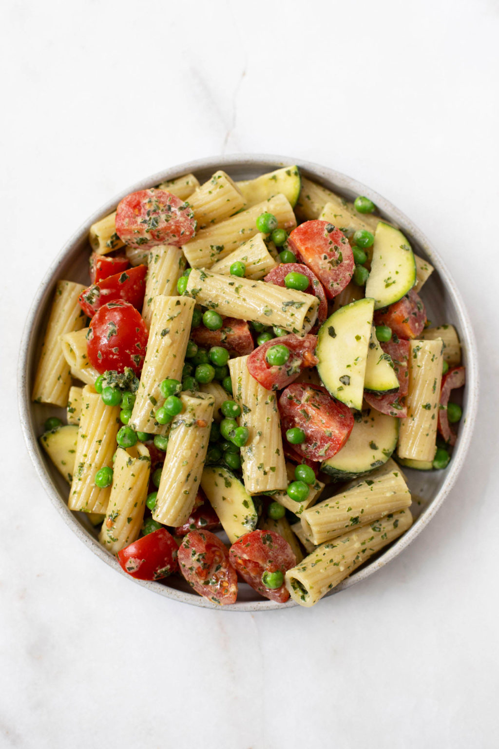 A round, white bowl holds a pasta salad that's made with a tahini base. The pasta salad is full of cherry tomatoes and peas.