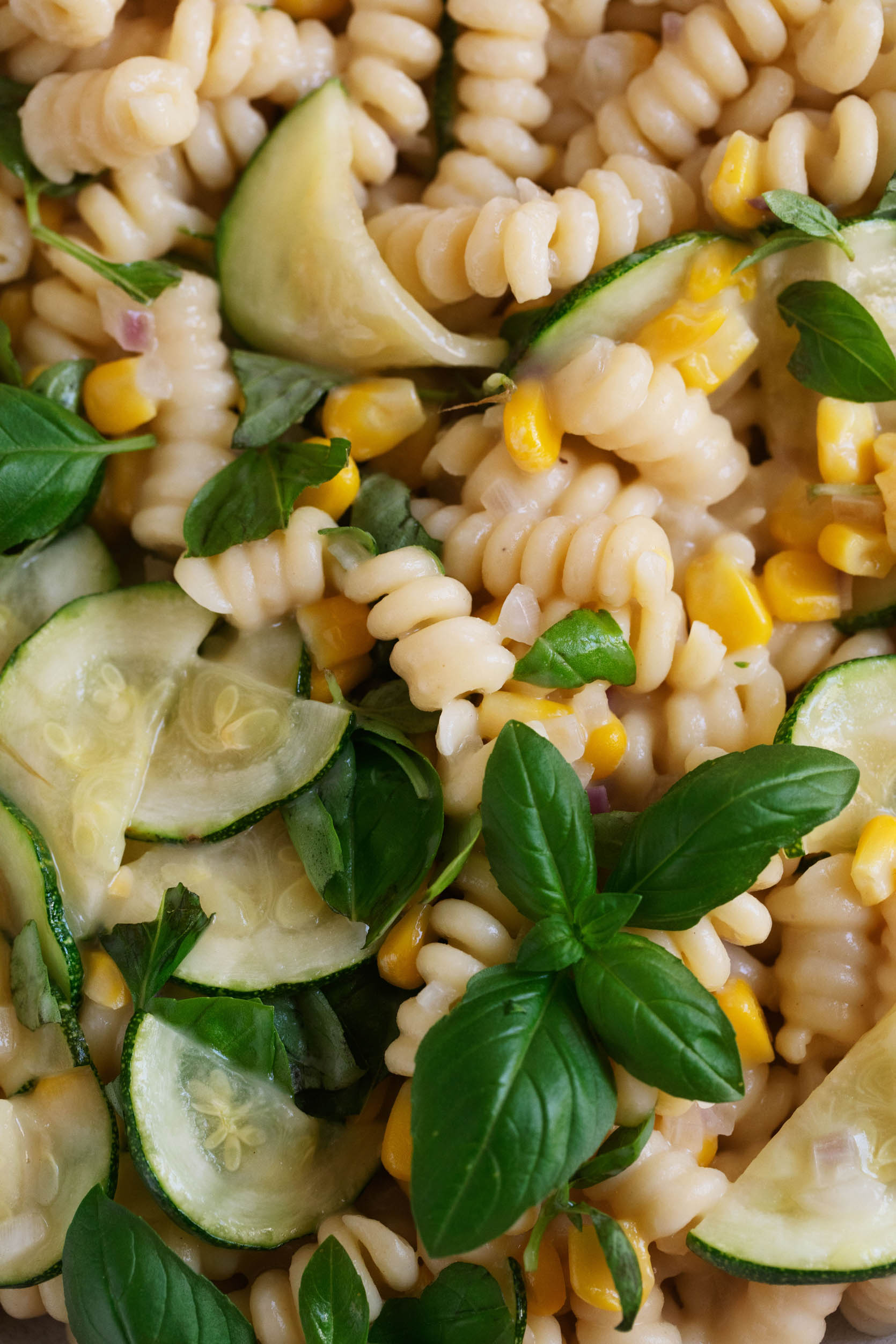 Zoomed in close up of a vegan pasta dish with zucchini, corn, and creamy sauce