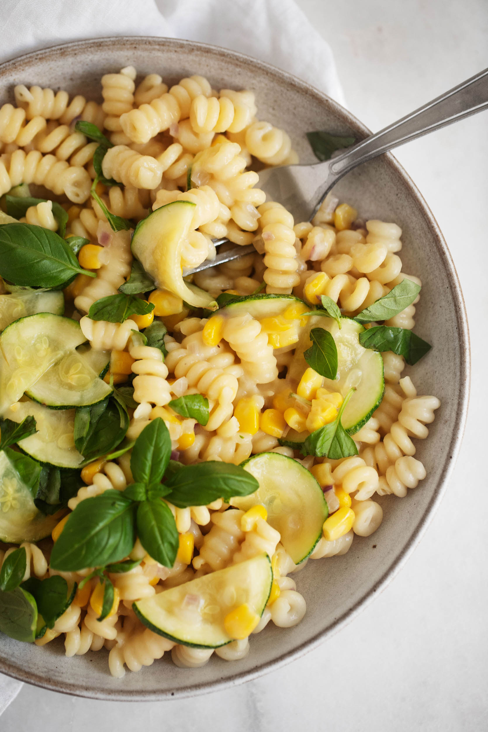 A vibrant dish of pasta with sweet summer corn, zucchini, and herbs