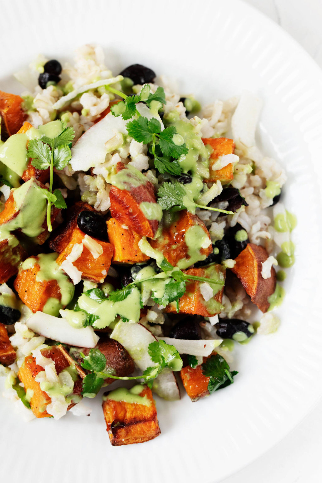 An overhead image of sweet potatoes, brown rice, and black beans. All of the ingredients are mixed with coconut chips and topped with a bright green dressing.
