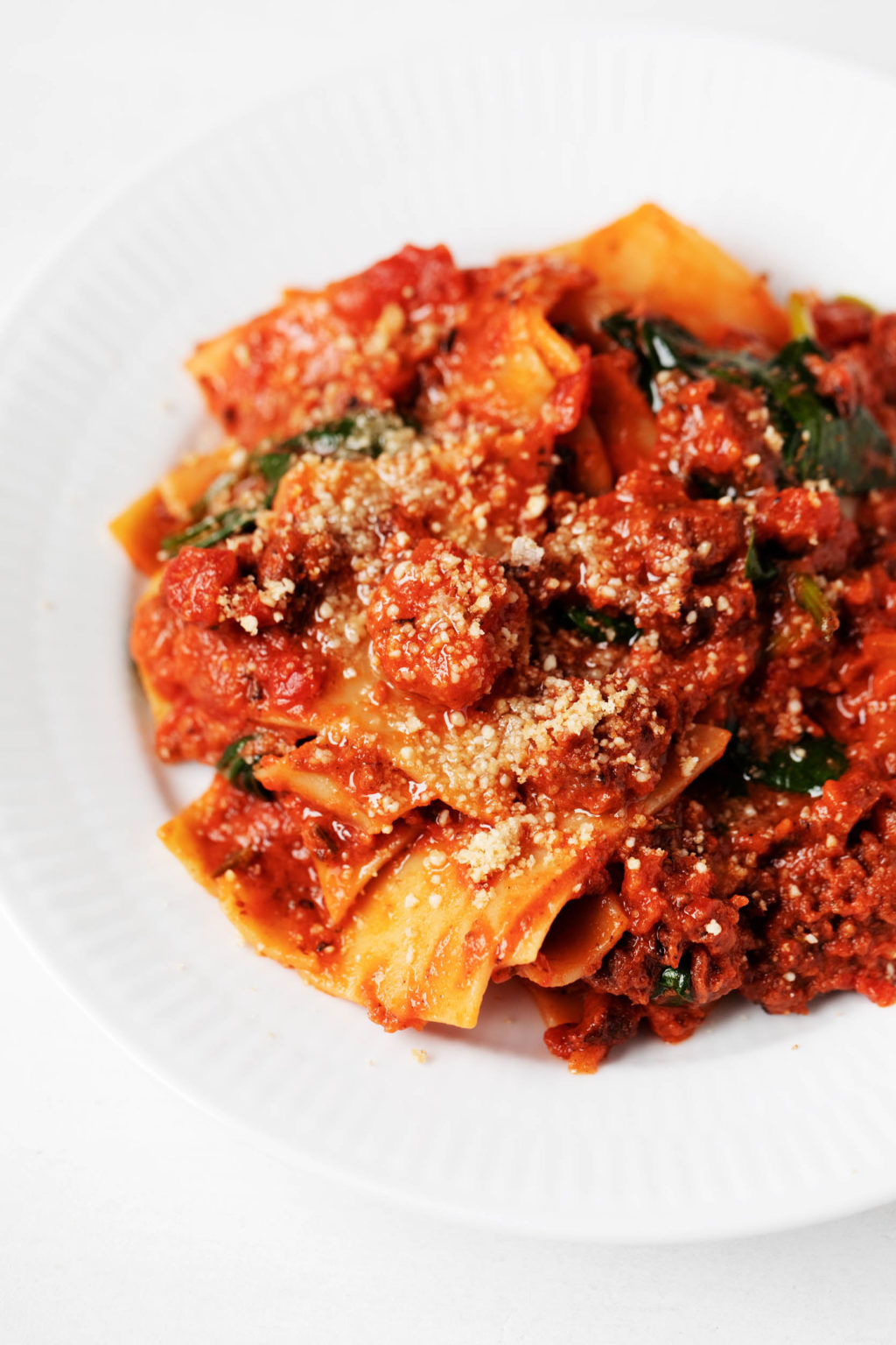 A white, shallow bowl has been piled high with a plant-based pasta dish, covered in red tomato sauce.