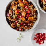 An overhead photograph of a bowl of sweet potatoes, pomegranate arils, and wild rice.