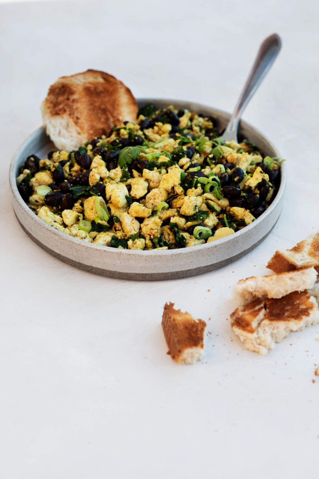 An angled photograph of a round plate, holding a vegan black bean tofu scramble with scallions and bread.