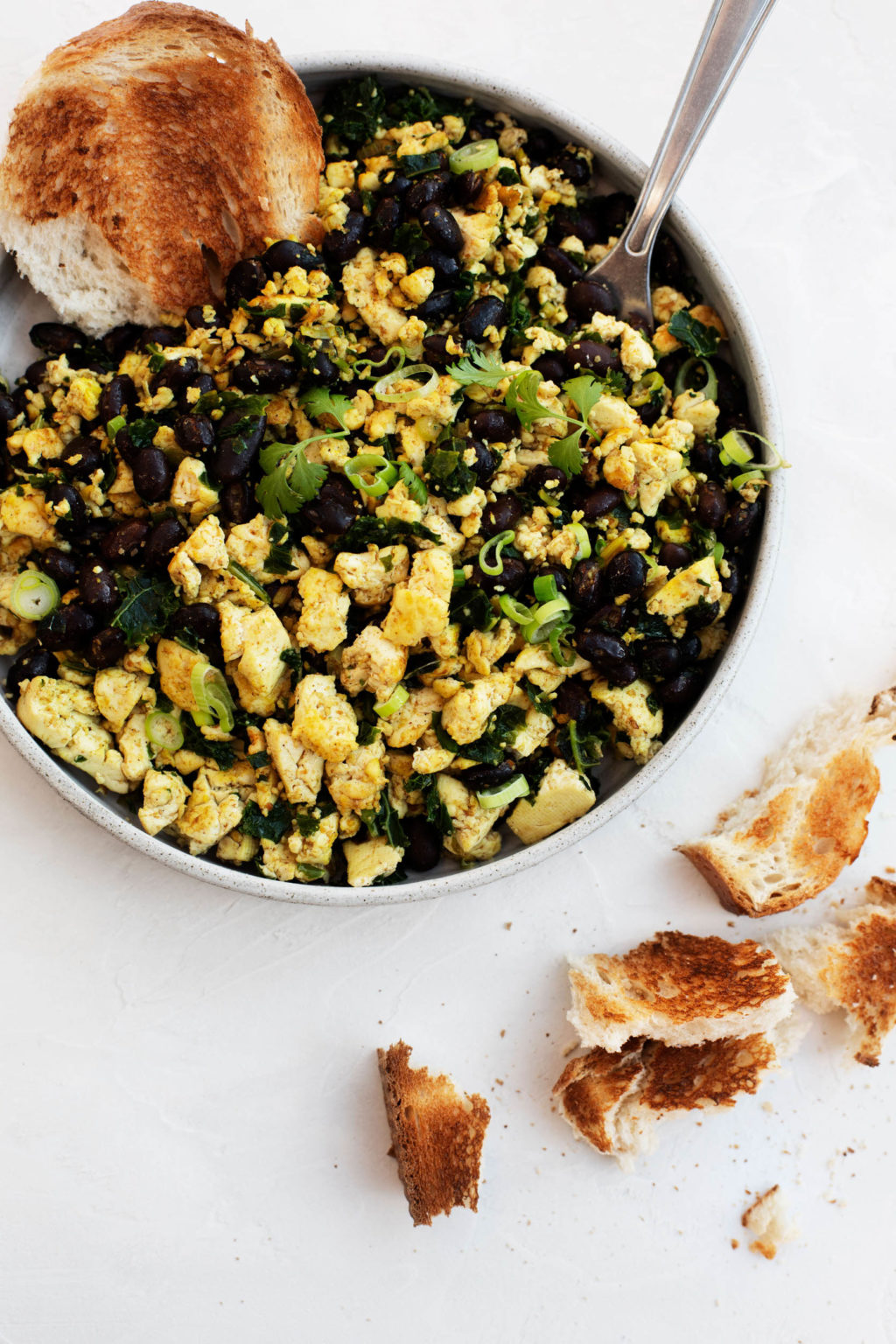 A large, round serving dish holds a savory vegan breakfast.