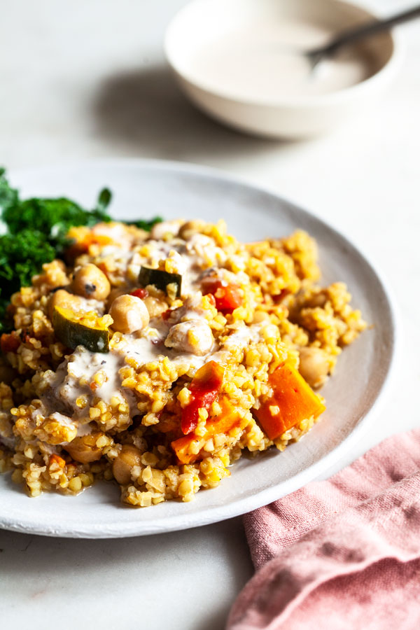 Simple Baked Bulgur & Chickpeas Dish Recipe - This dish of simple baked bulgur & chickpeas is rich in fiber, protein, an array of phytonutrients, and it's easy to prepare. Served with a bright, creamy tahini dressing! #chickpeas #dish #bakedbulgur #maindish #easydinnerrecipe
