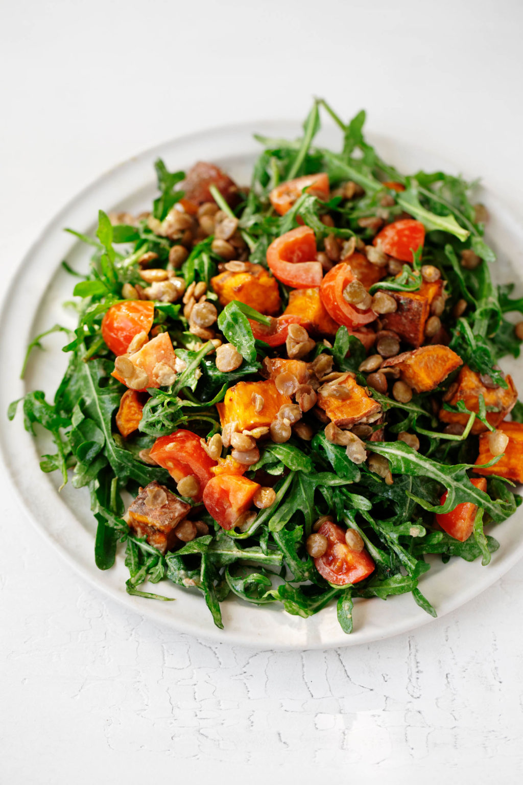 A round white plate has been covered in a colorful, creamy lentil tahini sweet potato salad.