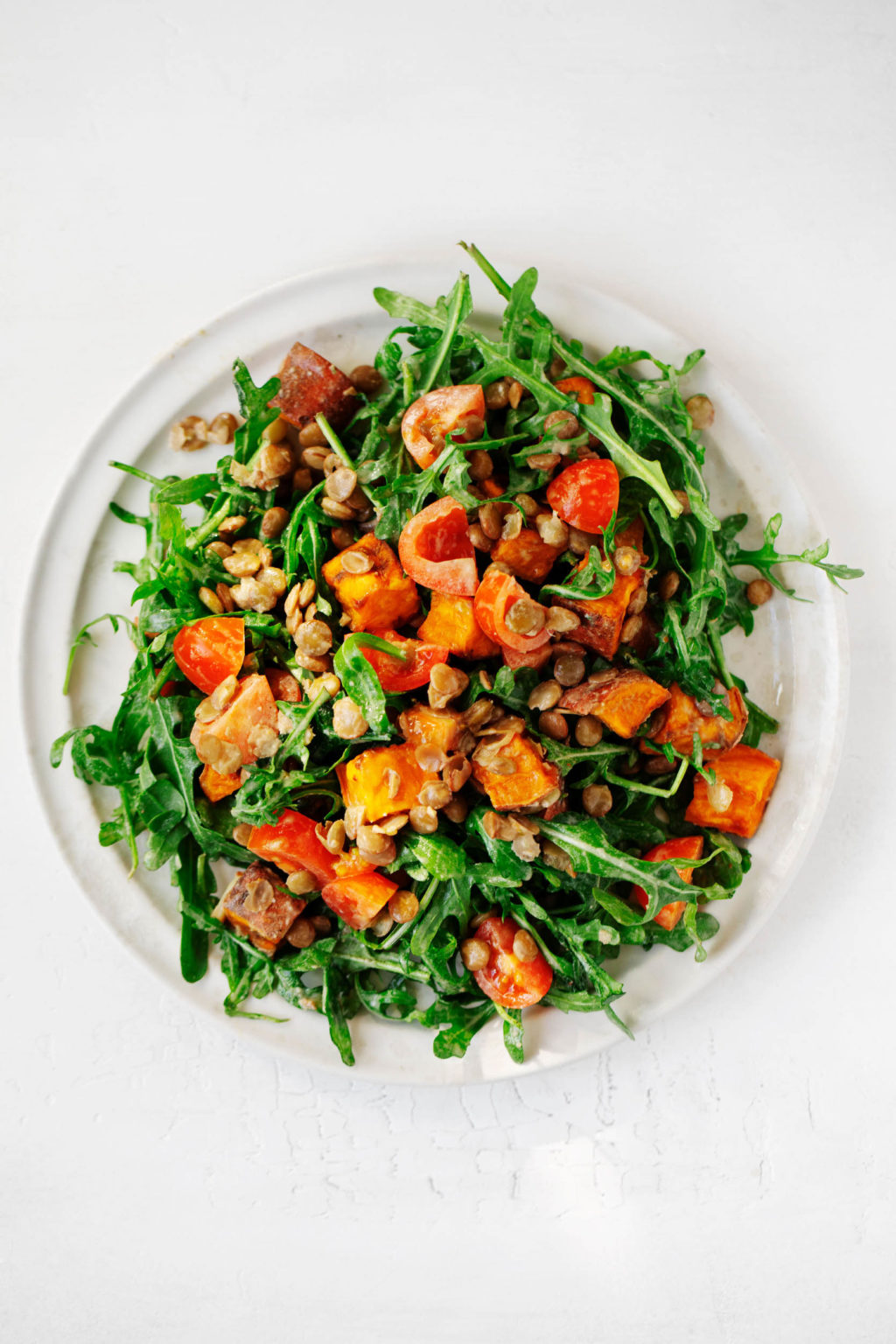 A round, white salad plate has been piled with arugula, sweet potatoes, grape tomatoes, lentils, and a creamy dressing.