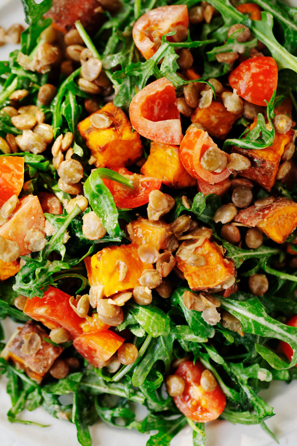 A close up image of a mixture of salad greens, roasted sweet potatoes, grape tomatoes, and lentils.