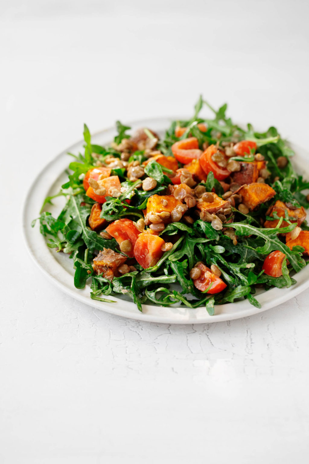 An angled photograph of a white plate covered with a plant-based, lentil tahini sweet potato salad..