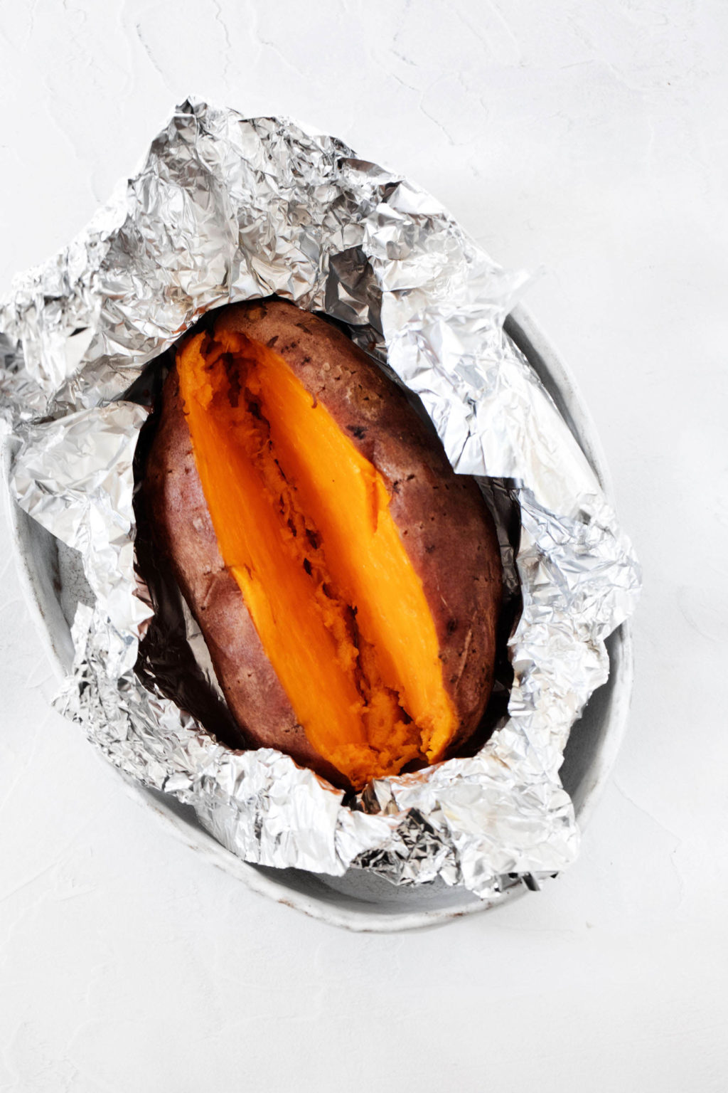 A roasted sweet potato is being stored in crumpled aluminum foil.