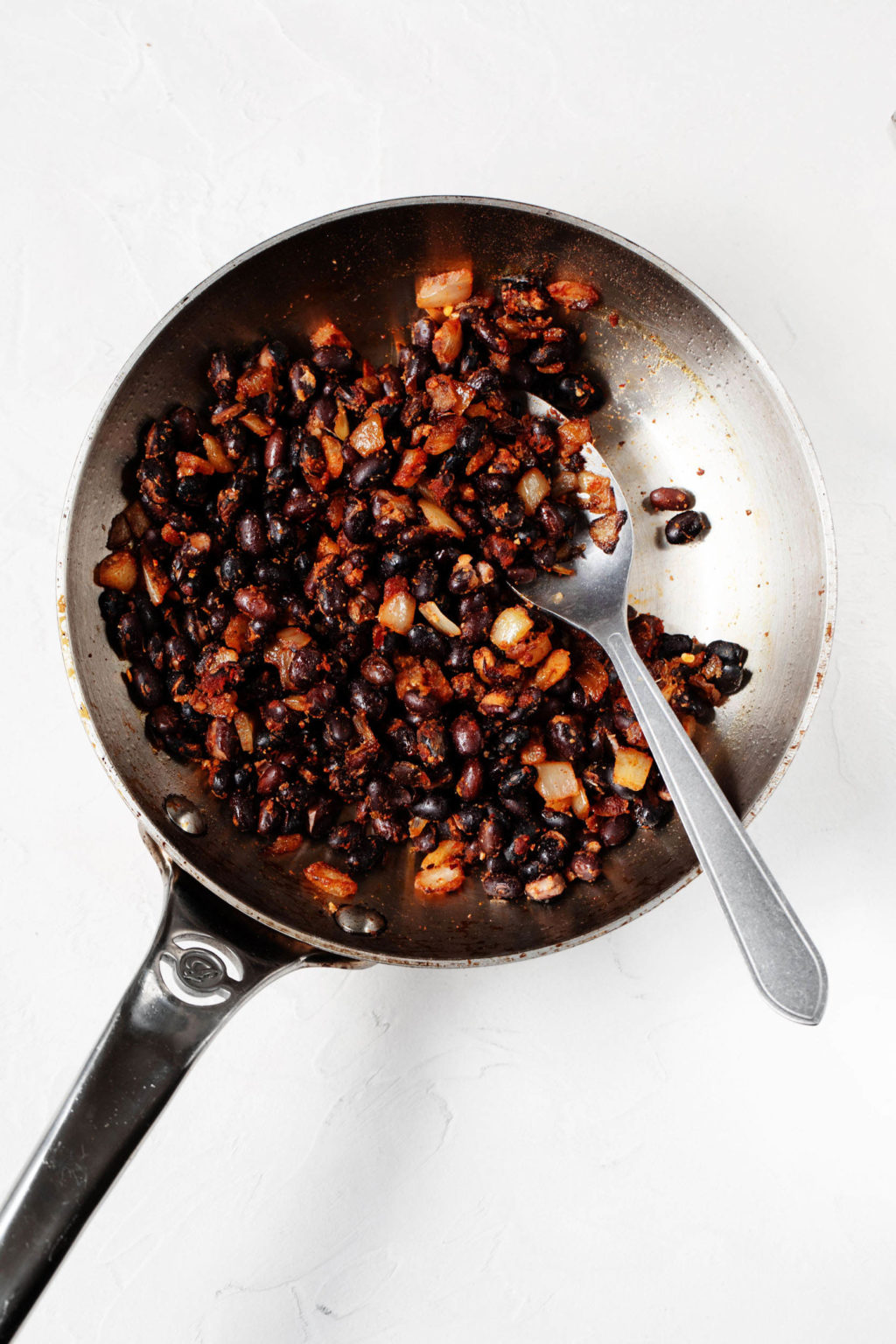 Black beans and onions are being sauteed in a round, stainless steel frying pan.