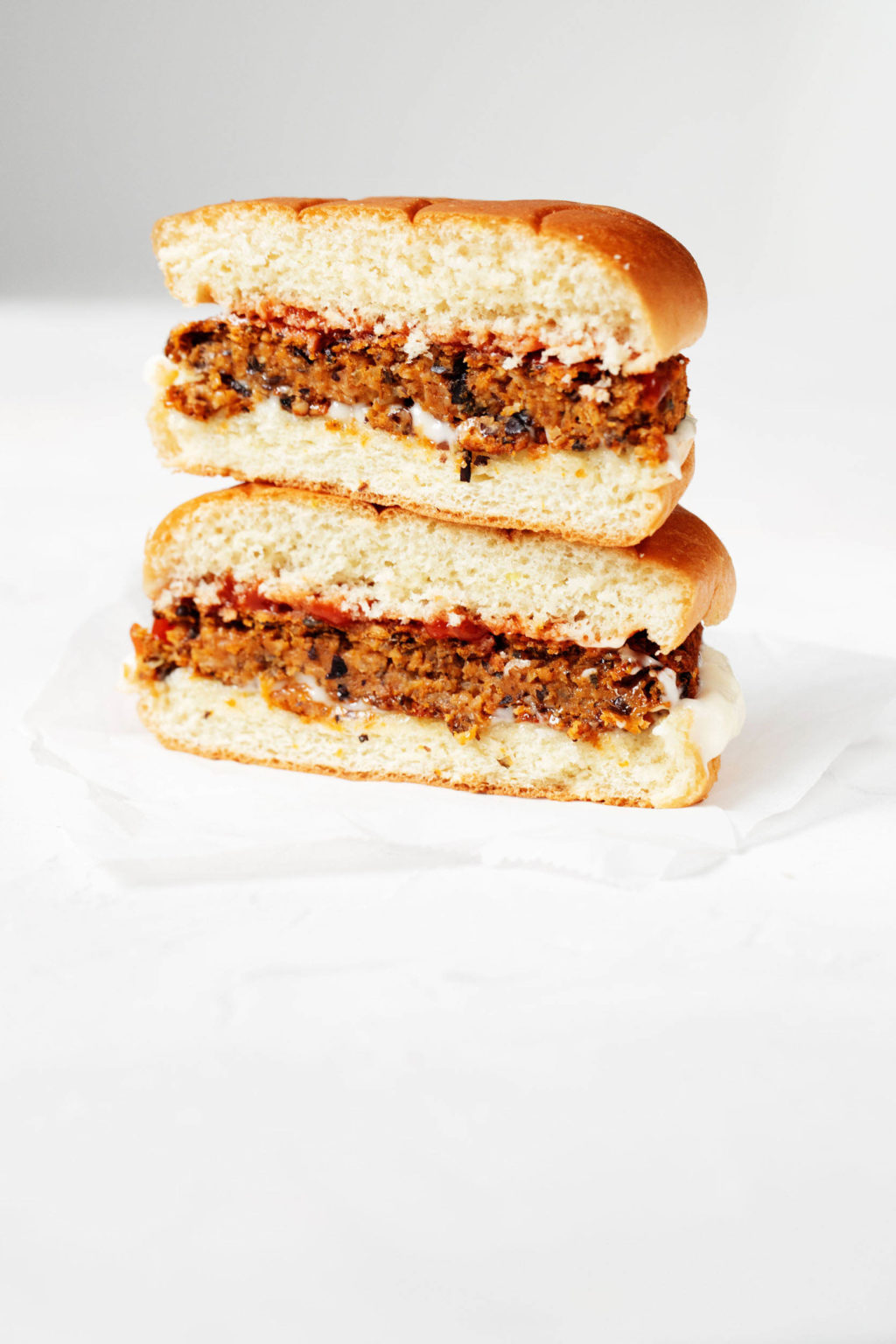 Vegan black bean sweet potatoes are served on a hamburger bun with ketchup and mayonnaise. The burger is cut in half, revealing a crosswise section.