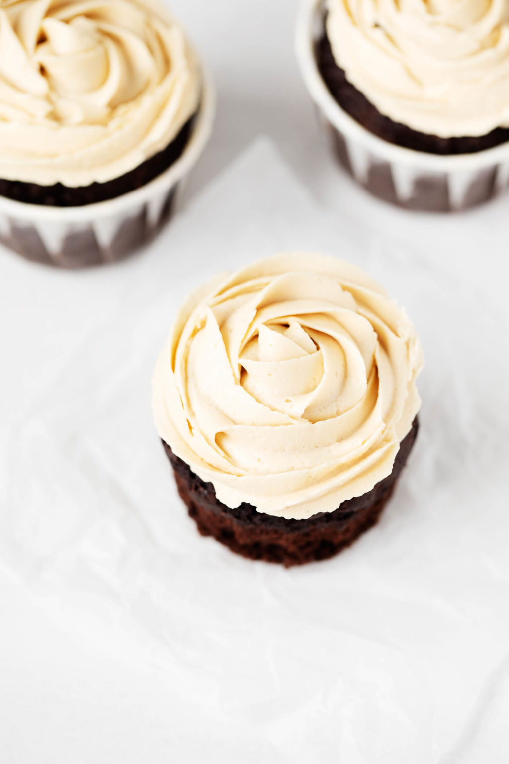 Three cupcakes with a dark base and a light, whipped frosting are positioned on a parchment paper surface.
