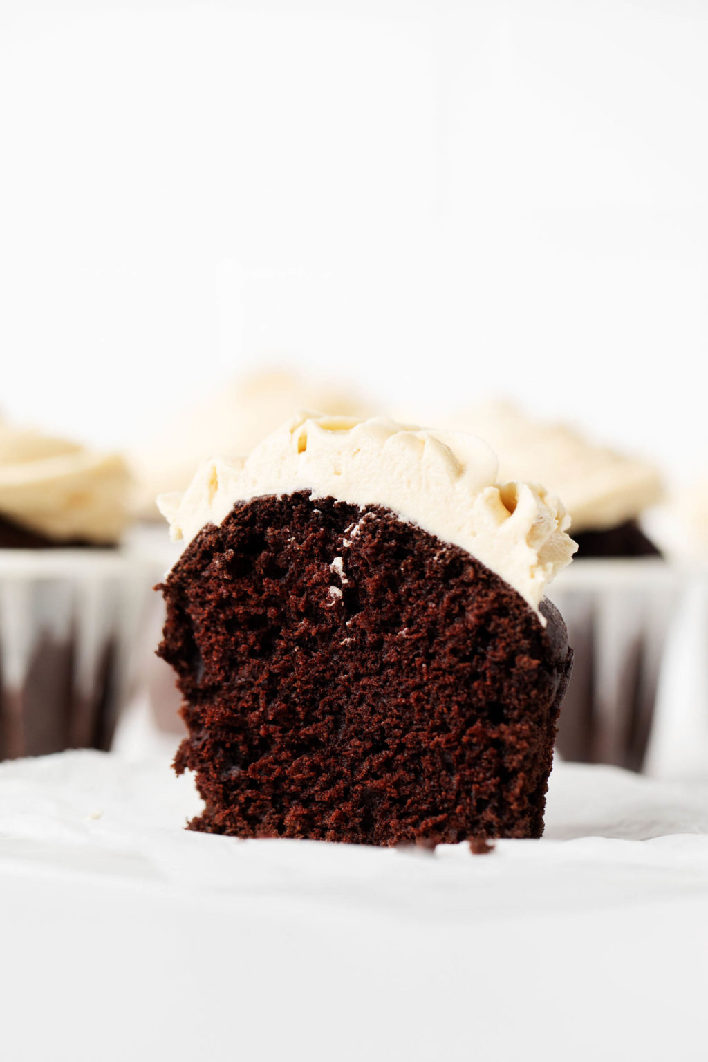 A vegan chocolate peanut butter cupcake has been sliced neatly in half. A cross section of the muffin is visible, with muffins that are still in their liners in the background.