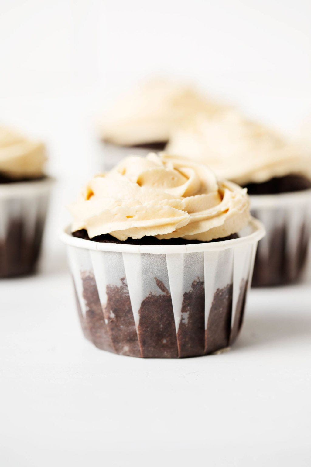 A sideways photograph of vegan chocolate peanut butter cupcakes, which have been piped with a creamy frosting.