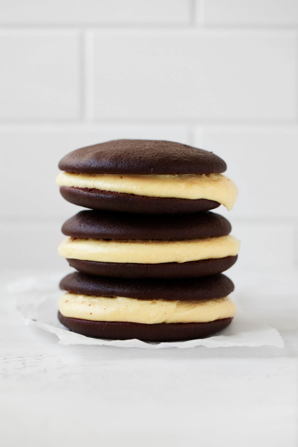 A sideways photograph of a neat stack of vegan Halloween whoopie pies, made with soft chocolate cookies and pumpkin cream.