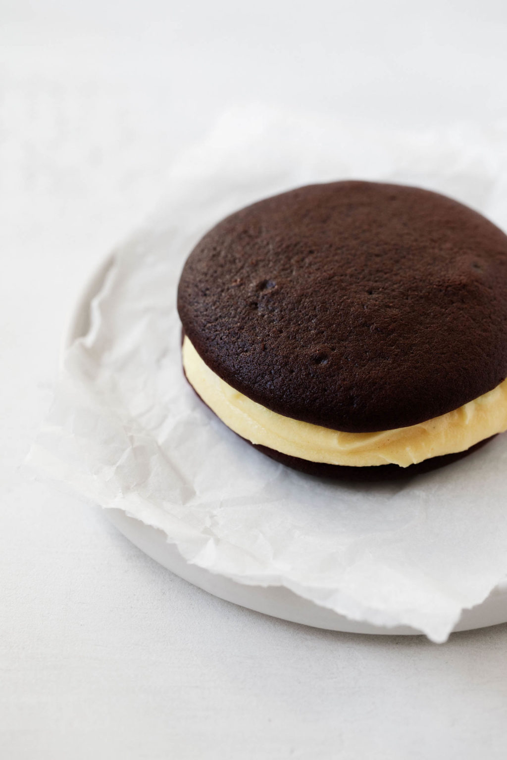 A chocolate and pumpkin vegan whoopie pie, served on a small dessert plate with a crumpled sheet of parchment.