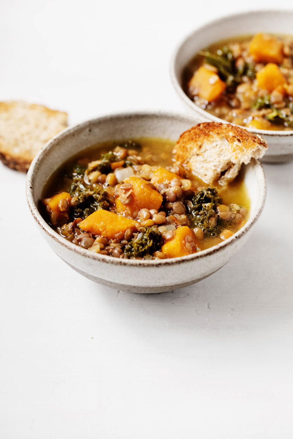 An angled photograph of two bowls of a vegan lentil, kale, and winter squash soup, which are served with toast points.