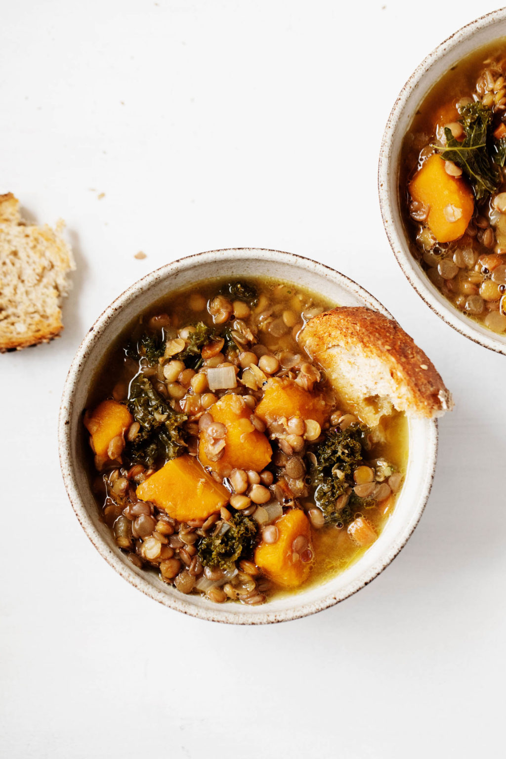 Two bowls of butternut kale lentil soup are laid on a white surface. A piece of toast rests nearby.