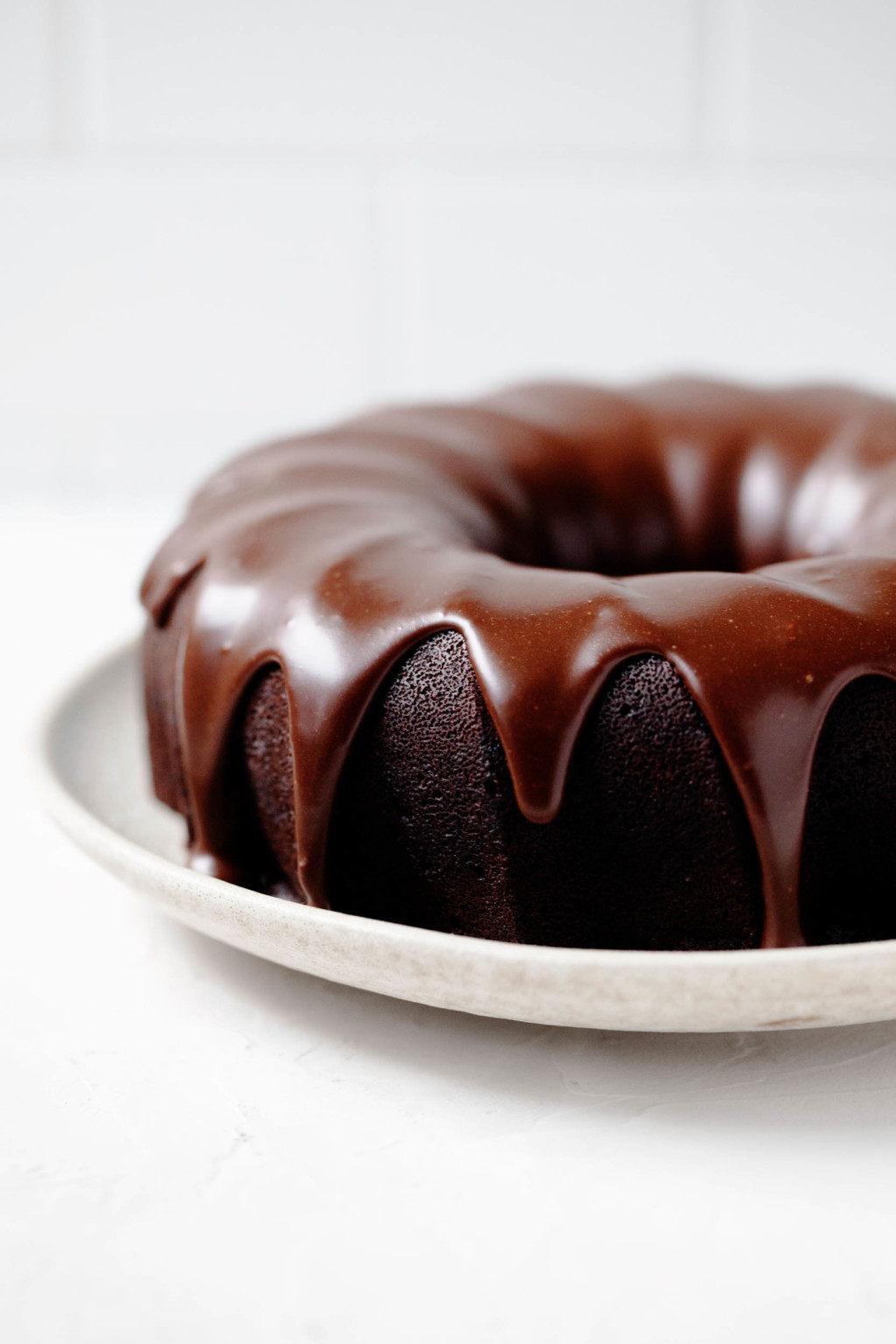 An angled photograph of a vegan chocolate bundt cake, which is placed on a serving platter and covered in a chocolate glaze.