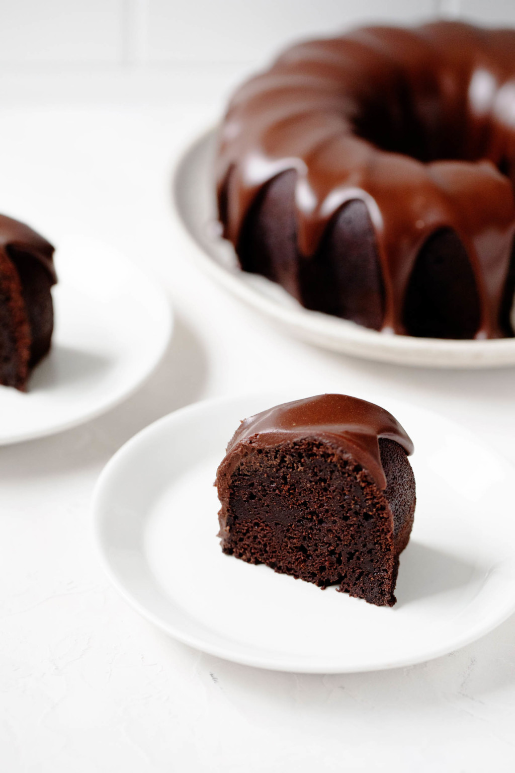 A slice of chocolate cake is on a small dessert plate in the foreground. The entire, glazed cake is sitting on a serving dish in the background.