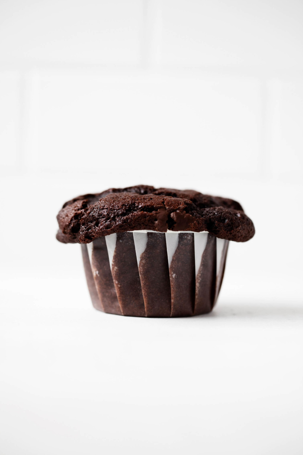 A single vegan chocolate muffin has been baked in a cupcake liner.