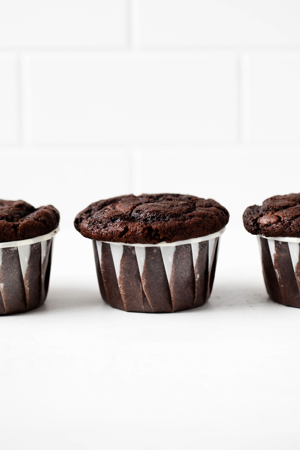 A few vegan double chocolate muffins have been lined up in a row, right in front of a white brick surface.