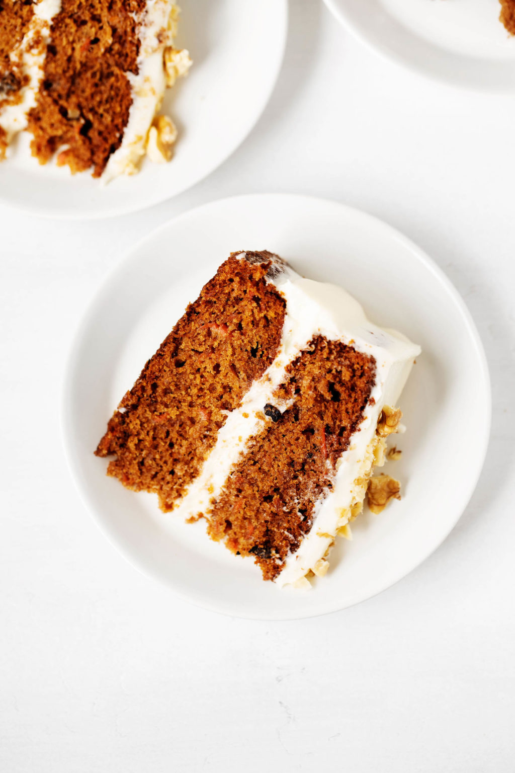 A neat slice of vegan carrot cake has been placed on a small dessert plate. Another slice peeks out in the background.