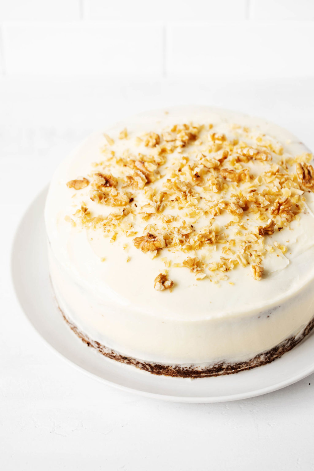 A frosted vegan carrot cake with chopped walnuts on top.