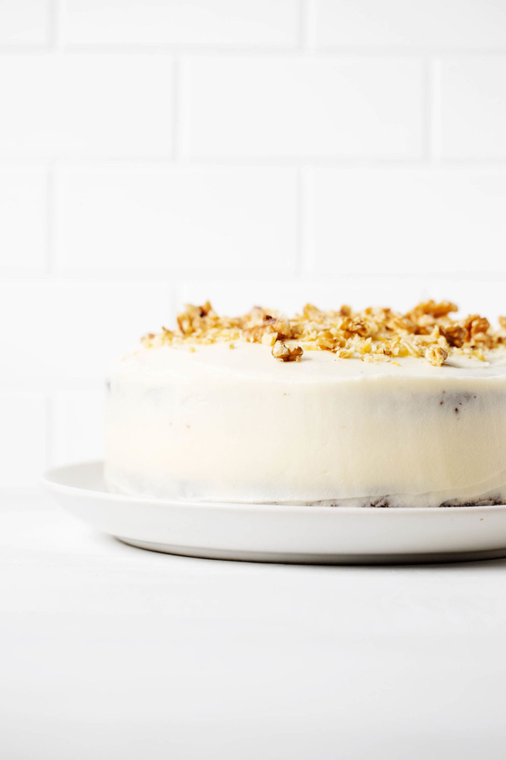 An angled photograph of a cake, which has been decorated with white frosting and chopped walnuts. It's resting on a white surface and against a white brick backdrop.