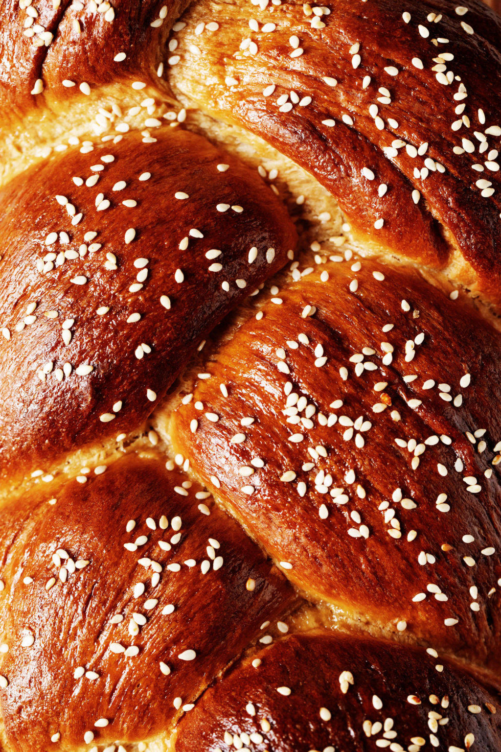 A close up, overhead image of a deep brown, baked and braided loaf of bread. It has been topped with sesame seeds.