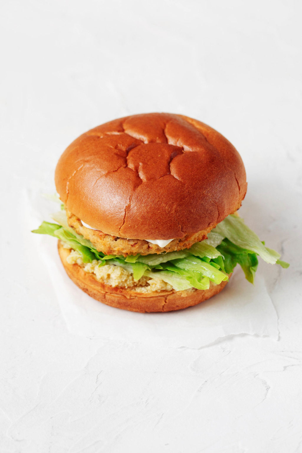 A vegetable based burger is served on a fluffy burger bun. It rests on a white sheet of parchment.