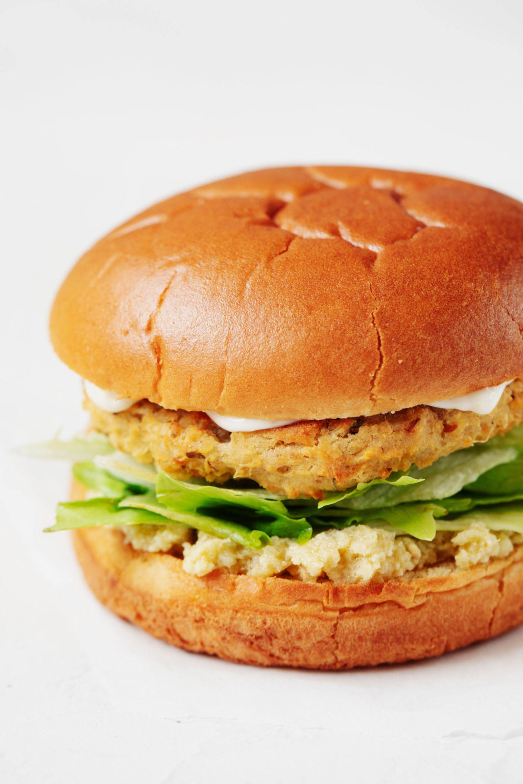 A close-up photograph of a plant-based patty, served on a fluffy bun with lettuce and a creamy spread.