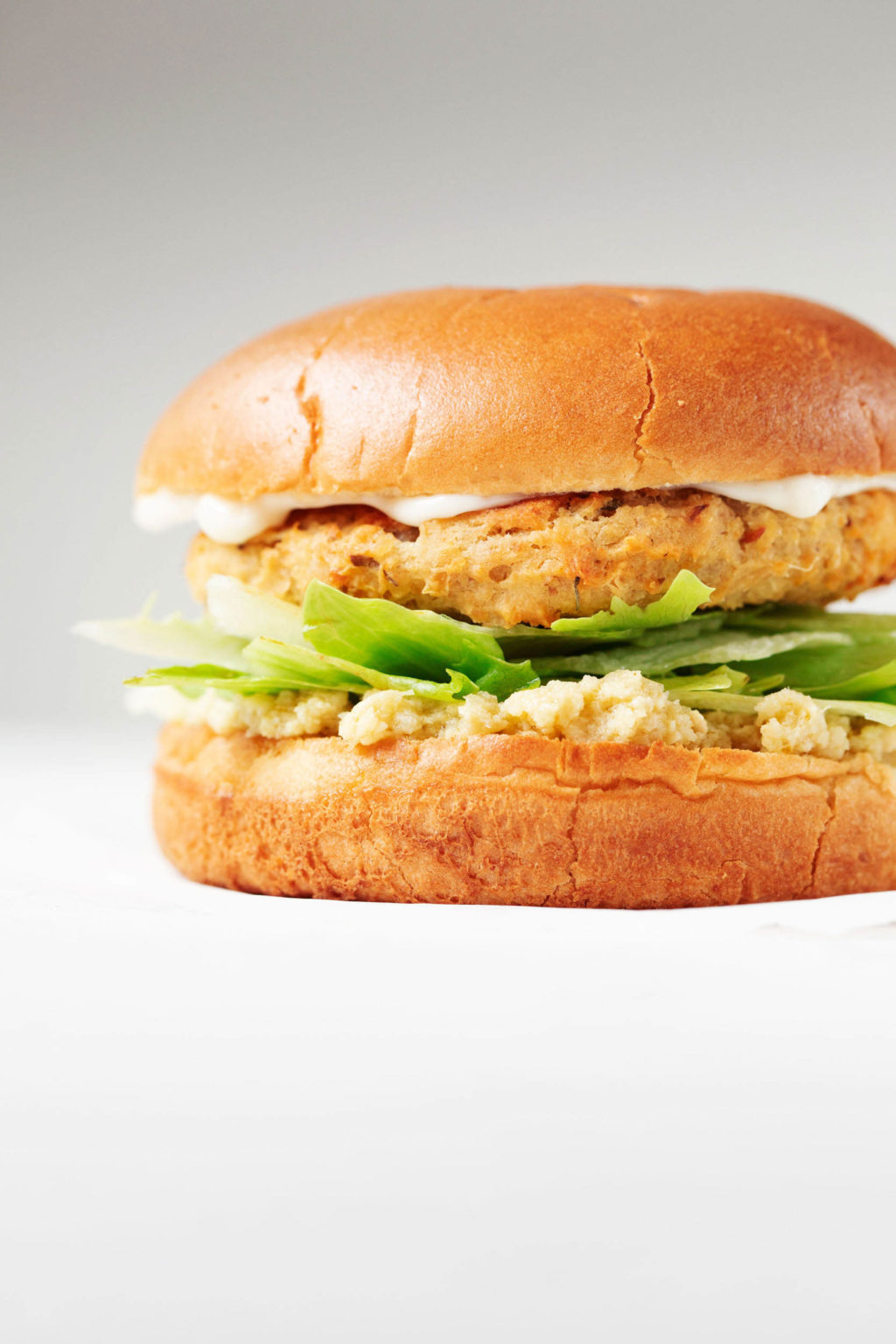 An angled photograph of a vegan artichoke white bean burger, served on a bun with greens and a creamy dip.