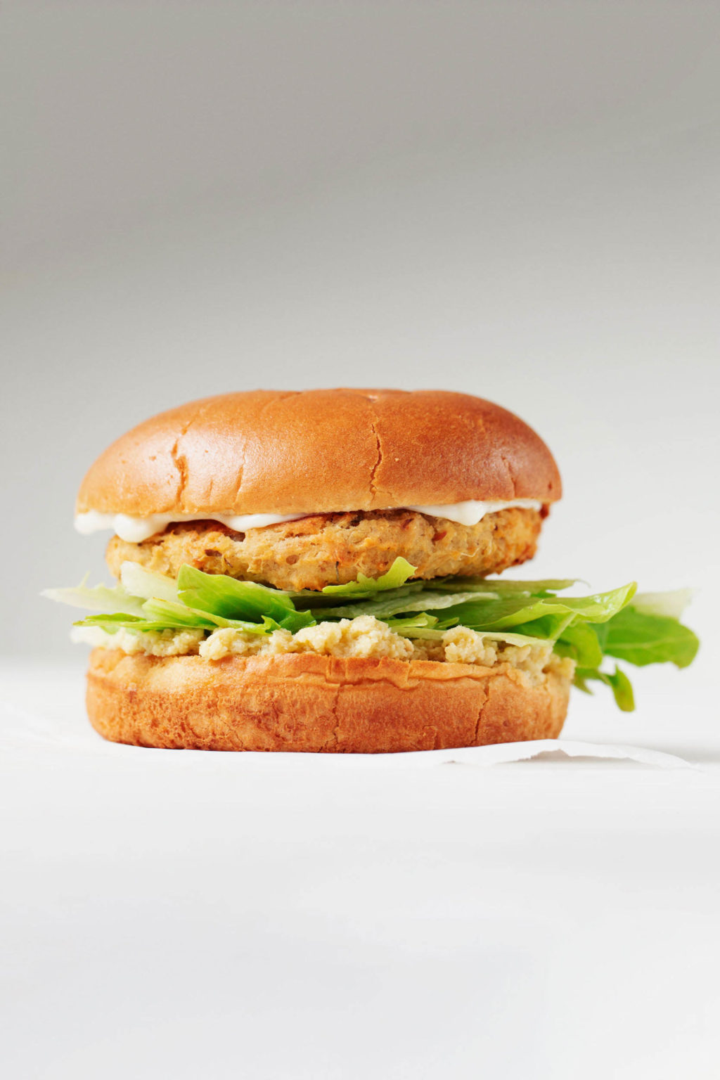 A sideways photograph of a vegetable burger on a bun, with lettuce and other toppings. It's on a white surface and photographed against a gray backdrop.