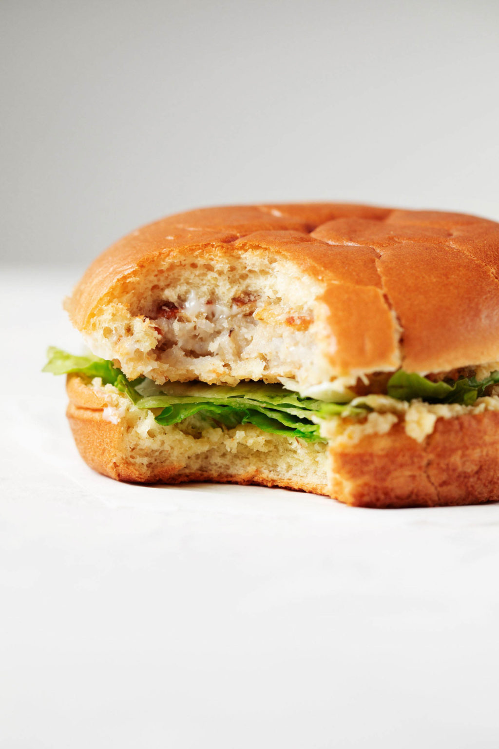 An artichoke white bean burger is piled onto a burger bun. A single bite has been taken out of the burger.