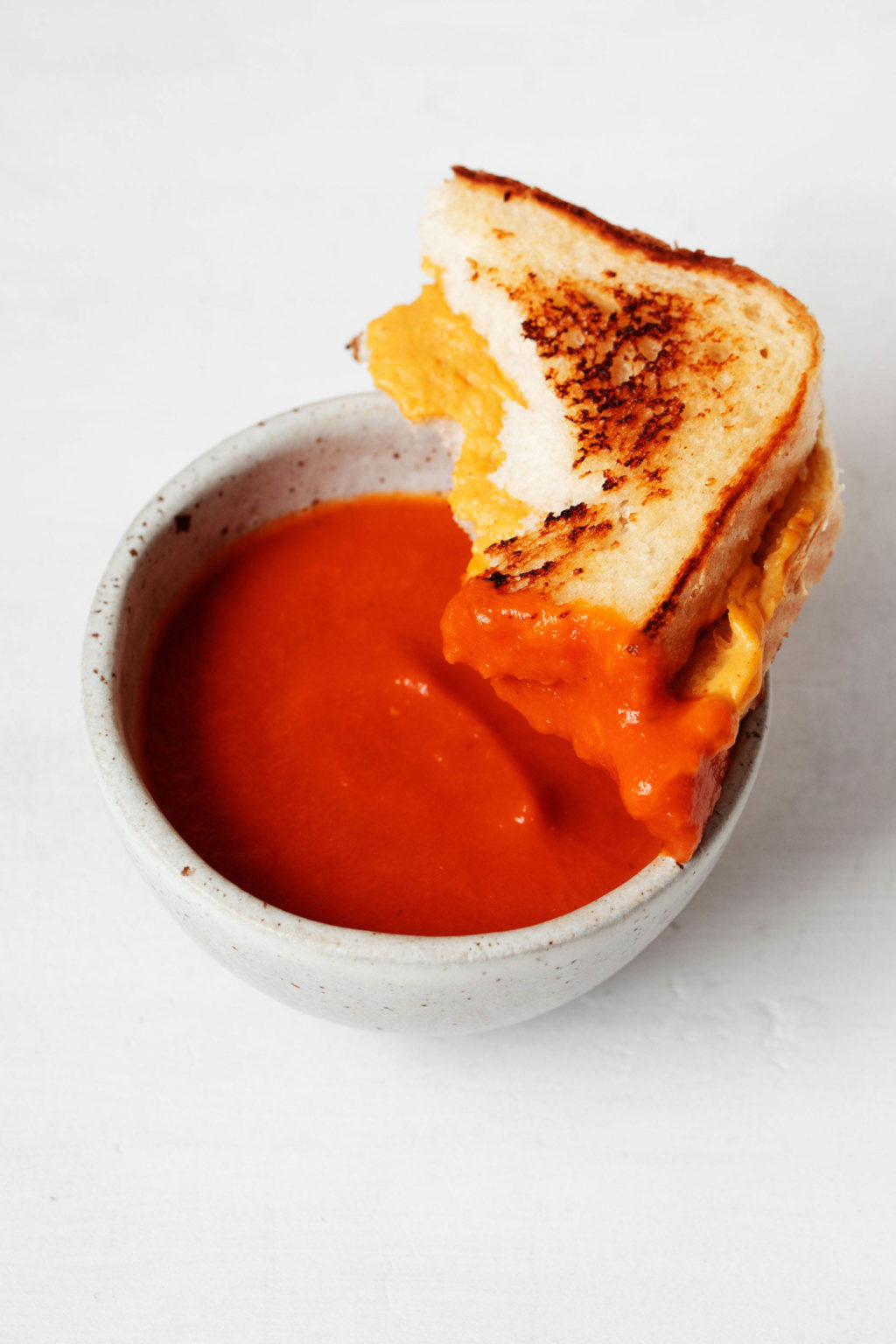 A small, white bowl of tomato soup has been dipped into with a half of a vegan grilled cheese sandwich.