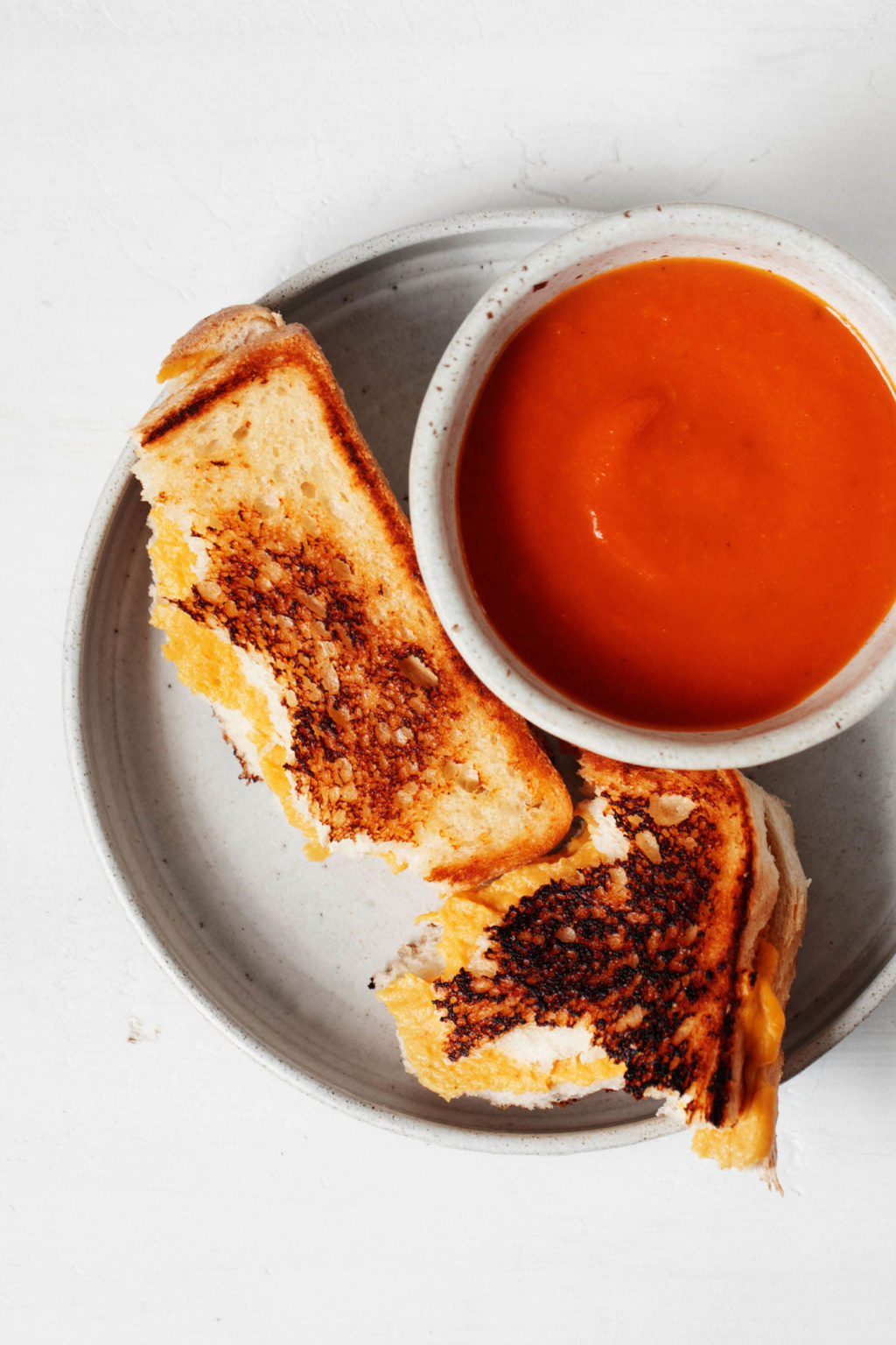A small bowl of tomato soup is accompanied by a crispy vegan grilled cheese. Both rest on a small, round white plate.